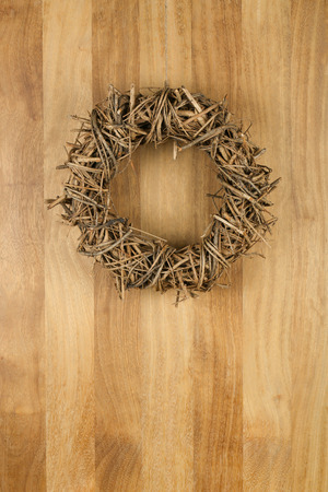 Christmas door wreath light brown twigs on sapele wood background, copy space photo
