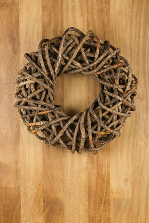 Christmas door wreath brown twigs on sapele wood background, copy space photo