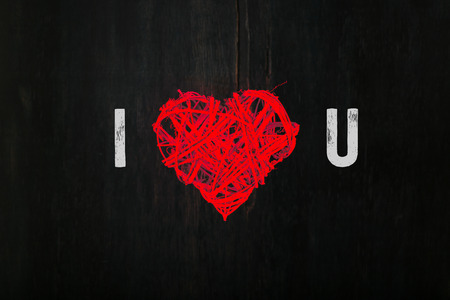 i love you sign: Romantic love message Valentines red wickers heart shaped wreath on dark background