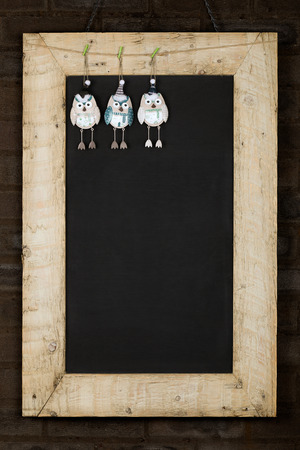 Merry Christmas and Happy New Years chalkboard blackboard tin owl decoration restaurant vintage menu design on painted reclaimed wooden frame isolated on dark brown brick wall Stock Photo