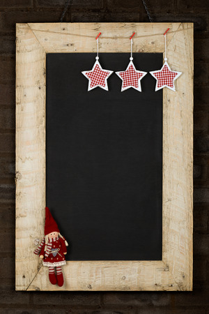 Merry Christmas and Happy New Years chalkboard blackboard stars and puppet decoration restaurant vintage menu design on painted reclaimed wooden frame, dark brown brick wall, copy space