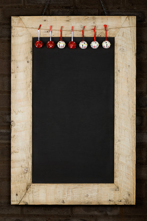 reclaimed: Merry Christmas and Happy New Years chalkboard blackboard bells decoration restaurant vintage menu design on painted reclaimed wooden frame, dark brown brick wall, copy space Stock Photo