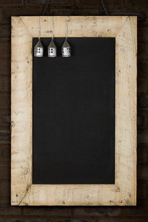 reclaimed: Merry Christmas and Happy New Years chalkboard blackboard tin houses decoration restaurant vintage menu design on painted reclaimed wooden frame, dark brown brick wall, copy space Stock Photo