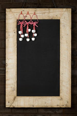 Merry Christmas and Happy New Years chalkboard blackboard tin bells decoration restaurant vintage menu design on painted reclaimed wooden frame, dark brown brick wall, copy space