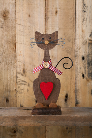 Valentines love brown wooden cat shape with red heart and gingham ribbon decoration on old rough grey background with copy space photo