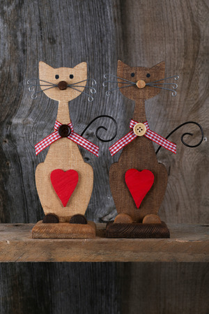 Two Valentines love brown wooden cats with red heart and gingham ribbon decoration on old rough grey background with copy space photo