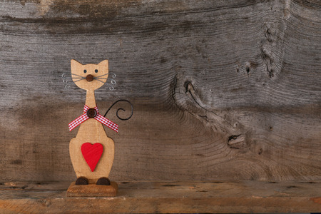 Valentines love brown wooden cat with red heart and gingham ribbon decoration on old rough grey background with copy space photo