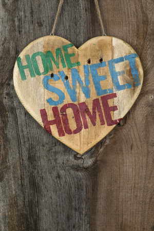 Home Sweet Home message wooden heart sign on grey background