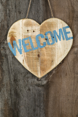 homecoming: Welcome message wooden heart sign from recycled old palette on rough grey wooden background, copy space
