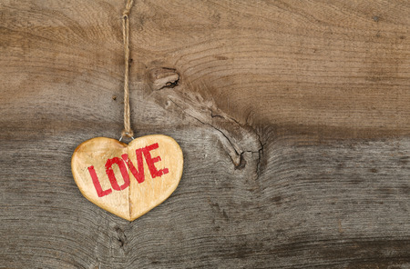 Love Valentines message wooden heart sign from recycled old palette on rough grey wood background, copy space Stock Photo
