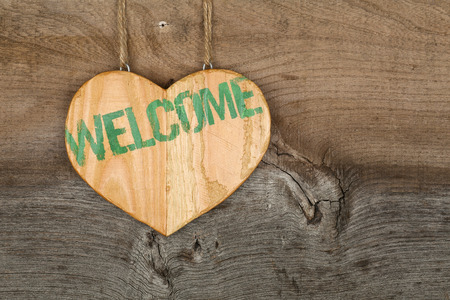 Welcome message wooden heart sign from recycled old palette on rough grey wooden background, copy space photo