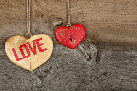 Love Valentines message two wooden hearts sign from recycled old palette on rough grey wood background, copy space