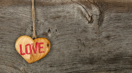 Love Valentines message wooden heart sign from recycled old palette on rough grey wood background, copy space photo