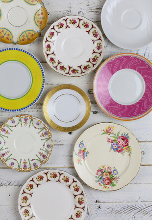 Set of plates with antique figure border pattern assorted vintage china on white painted rough wood background