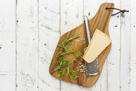 Parmesan chess with grater with fresh italian herbs on chopping board and rough white wood background, copy space Stock Photo