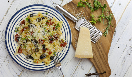 Italian pasta plate with green and black olives, sun dried tomatoes, oregano leaves and young green garlic, parmesan chess with grater with herbs on chopping board and rough white wood background