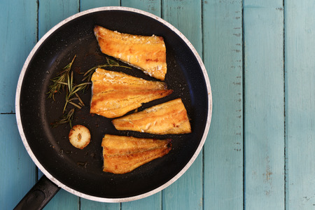 haddock: Four grilled smoked haddock fillets in cooking pan with rosemary brunch and garlic on turquoise background