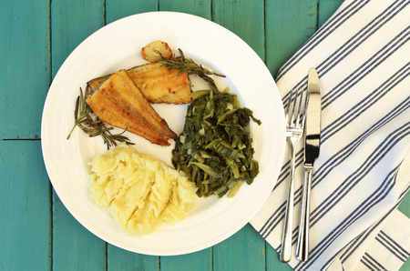 haddock: Grilled smoked haddock fillets with rosemary brunches mash potato and swiss chard on white plate, striped cloth fork and knife, turquoise background