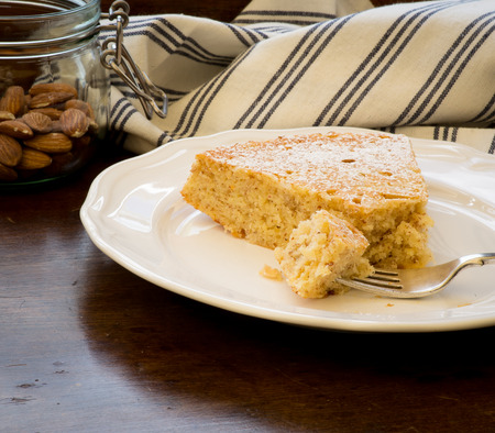lemon cake: Homemade sweet lemon cake with almonds and oat flour, glass jar with almonds, slice with fork on white plate, old wood table