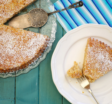 lemon cake: Homemade sweet lemon cake with almonds and oat flour on glass plate, slice with fork on white plate, painted turquoise table Stock Photo