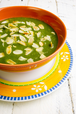 Swiss chard and potato cream soup with chopped roasted almonds in brown ceramic bowl Stock Photo