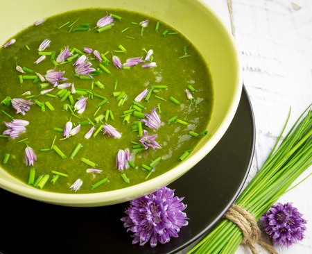 Swiss chard and potato cream soup with chopped chives with edible chives flowers in green ceramic bowl Stok Fotoğraf