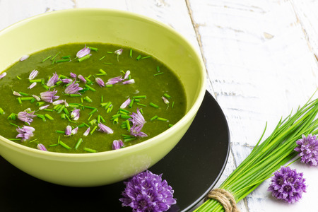 Swiss chard and potato cream soup with chopped chives with edible chives flowers in green ceramic bowl Imagens