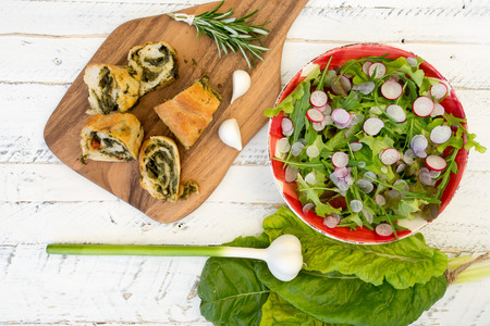 painted wood: Dough rolls strudel with swiss chard and chorizo on chopping board, young garlic with lettuce and rocket leaves salad, chopped radishes, white painted wood background Stock Photo