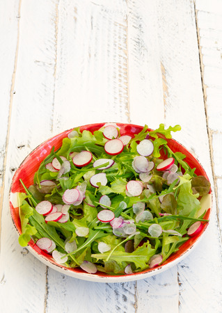 painted wood: Lettuce and rocket leaves salad with chopped radishes on gingham plate, white painted wood background, coppy space Stock Photo