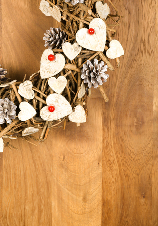 Christmas handmade vintage wreath decoration Shabby Chic white wooden hearts with red berries over wooden background - retro style design, copy space