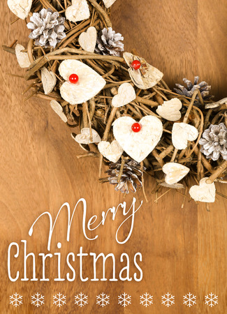 Merry Christmas message, handmade wreath decoration Shabby Chic white wooden hearts with red berries over wooden background - retro style design