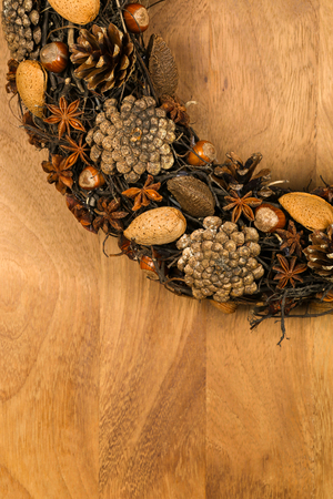 motivos navide�os: Christmas handmade natural wreath decoration pine cones, almonds, anise stars and hazelnuts over wooden background - retro style design, copy space