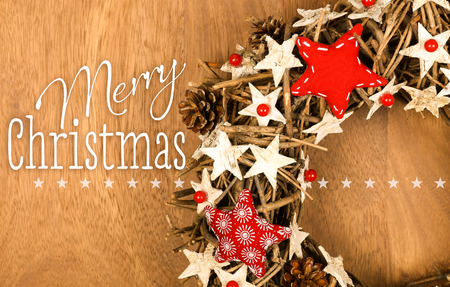 Merry Christmas message, handmade wreath decoration Shabby Chic white wooden stars with red gingham fabric pattern over wooden background - retro style design