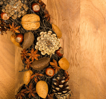 Christmas handmade natural wreath decoration pine cones, almonds, anise stars and hazelnuts over wooden background - retro style design, copy space