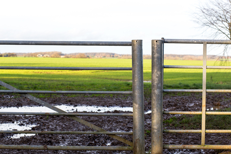 iron fence: Old field gate by a roadside, rural England scene of fields and meadows in thebackground