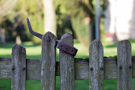 Old wooden fence door with metal latch leading to an English village church