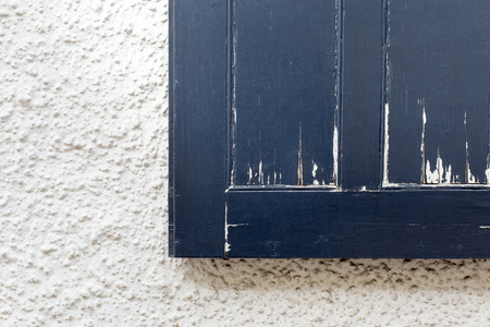 peeling paint: Old dark blue rough vintage window shutter with peeling paint on white wall, copy space background Stock Photo