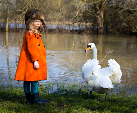 oxford: Oxford, United Kingdom, March 16, 2016: Young girl in orange coat with white swan in Oxford University Parks by the Cherwell river
