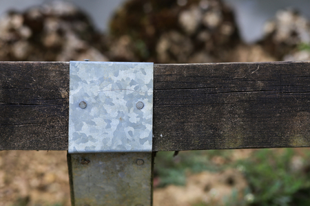galvanised: Galvanised steel sheet cover for old wood fence post joint around the pond