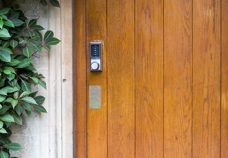 Simple door handle electronic lock with numeric buttons on old wooden door Stock Photo