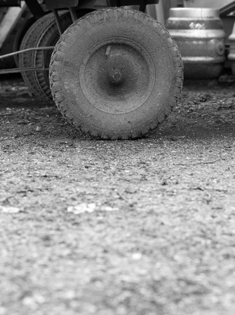pneumatic: Old dirty pneumatic wheel of small cart in courtyard Stock Photo