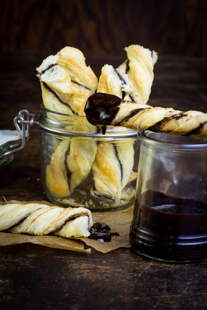 twists: Homemade danish puff pastry twists dipped into melted chocolate in small jar on dark background