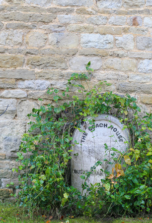 letras negras: The Coach House Buckingham white painted stone with black letters overgrown with green leaves vines with stone wall