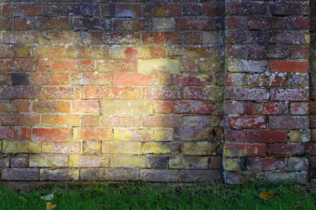 Old brick wall with large yellow sun spot and green grass