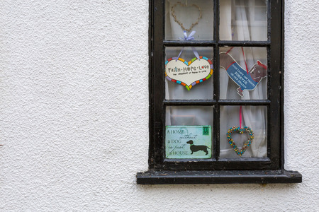 Cute cottage black window with decorative signs on white painted cottage wall, home of dachshund Stock Photo