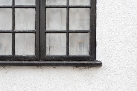 Black window frame with condensation drops on white painted cottage wall, copy space