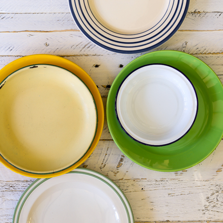 Set of plates with vintage shape border pattern assorted ceramic china on white painted rough wood background Stock Photo