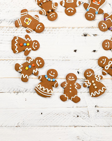 Christmas homemade gingerbread man family cookies couples on white wooden table background, International friendship concept