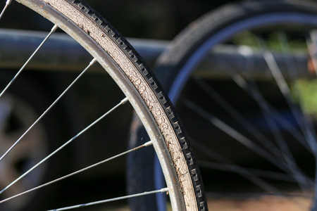 Close up shot of old bicycle wheel rim with tire on dark background Stock Photo