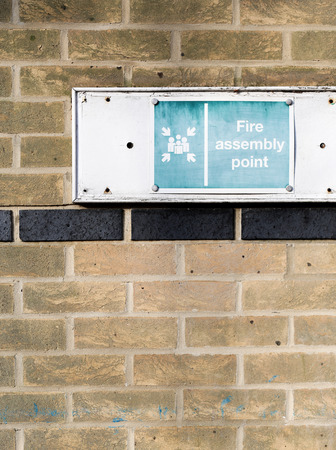 assembly point: Faded assembly point sign on light brown brick wall Stock Photo